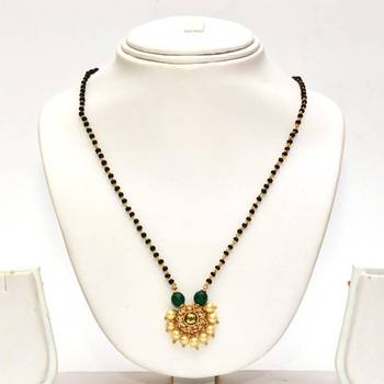 Anvi's black beads chain with uncut stones centered with emerald