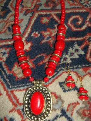 red stone necklace in dull gold with red beads and matching earrings